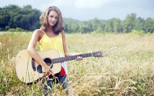 Blond woman with a guitar, standing in a field for Jesus